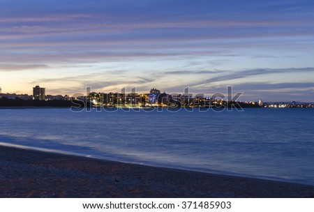 Mooloolaba after sunset. Mooloolaba bay and beach in foreground. Mooloolaba Beach and esplanade with lights turned on in buildings and streetlights in midground. Pink and bluea cloudscape after sunset.