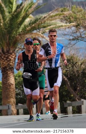 "MOOLOOLABA, AUSTRALIA - SEPTEMBER 14 : Pros Dan Wilson (green), Brad Kahlefeldt (blue) , Courtney Atkinson (black) in the ""Ironman 70.3"" triathlon on September 14, 2014 in Mooloolaba, Australia - stock photo"