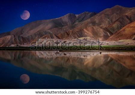 Moon and mountains reflected in the Kara Kul lake, Karakorum mountains, Xinjang province, China - stock photo