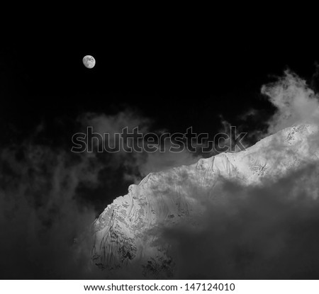 Moon and slope of the Nuptse (7864 m) at sunset (view from Kala Patthar) - Everest region, Nepal (black and white) - stock photo