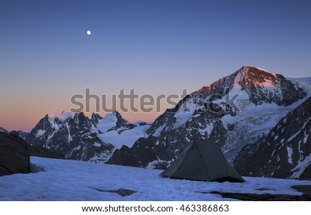 Moon and the last sunlight on the mountains at a campsite in the Swiss Alps.