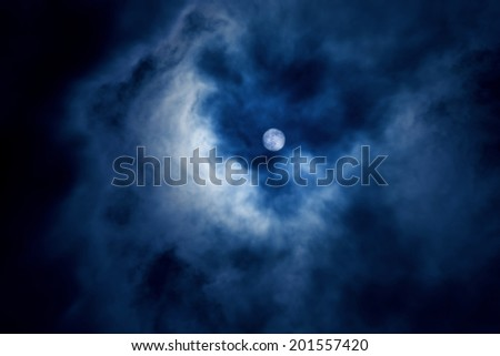 Moon behind the clouds - stock photo