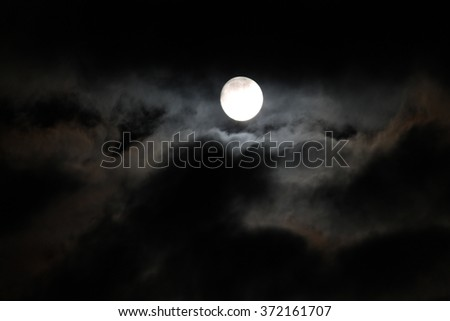 Moon between the clouds at night