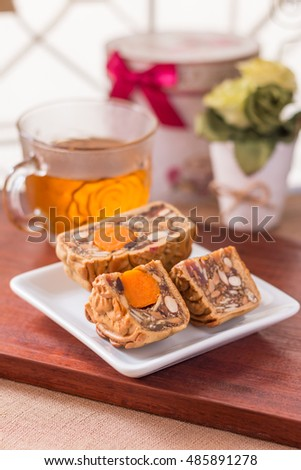Moon cake and tea - Chinese traditional moon cakes on white plate and table setting with teacup. Closeup, Select focus.