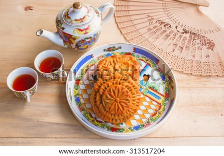 Moon cake and tea set on wooden table, Chinese mid-autumn food festival - stock photo