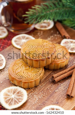 Moon cakes and tea with lemon and cinnamon around. Chinese mid autumn festival food.