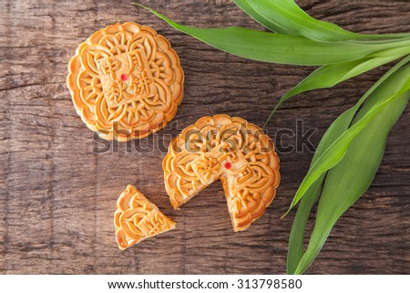 Moon cakes for the chinese Mid-Autumn festival and green leaf, on wooden background - stock photo