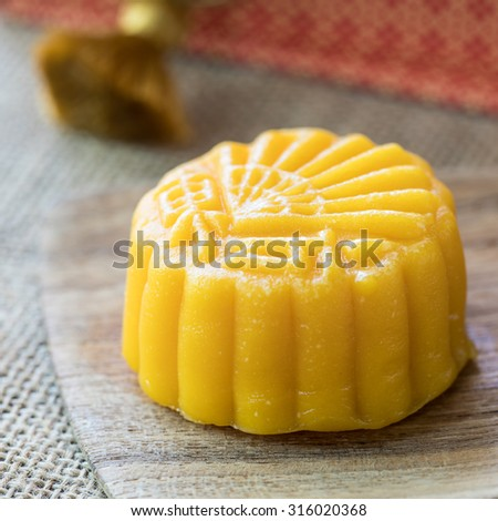 Moon cakes on wooden plate for the Chinese Mid-autumn festival - stock photo