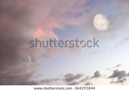 Moon clouds skies is a vibrant surreal fantasy like cloudscape with the ethereal heavenly full moon rising among the vibrant wispy colorful cloudscape. - stock photo