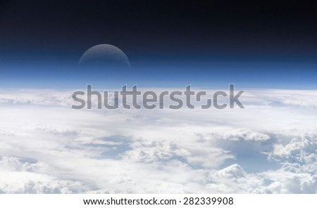 moon far away from the earth with clouds on the foreground.Some elements of this image furnished by NASA - stock photo