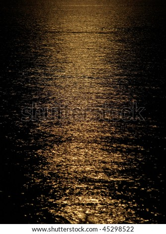 Moon light reflection on calm but rippled water - stock photo