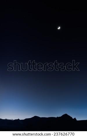 Moon on the Dark Blue Sky among mountains. Antarctica. - stock photo