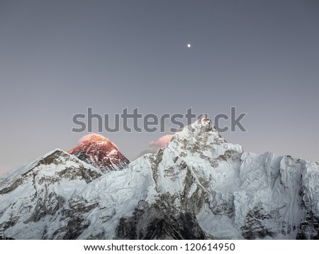 Moon over Mt. Everest (8848 m) and Nuptse (7864 m) at sunset (view from Kala Patthar) - Everest region, Nepal, Himalayas - stock photo