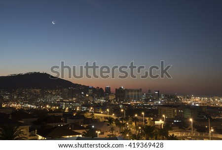 MOON OVER SIGNAL HILL ABOVE CAPE TOWN SOUTH AFRICA AT NIGHT - APRIL 2016 - A new moon and night view across the city of Cape Town South Africa