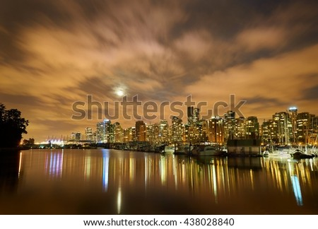 Moon Over Vancouver Night. The night skyline of downtown Vancouver, British Columbia, Canada, from Stanley Park. Evening as the the moon is rising.                                 - stock photo