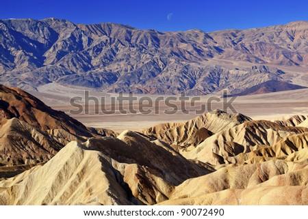 Moon Over Zabriskie Point Mudstones form Badlands  Death Valley National Park California - stock photo