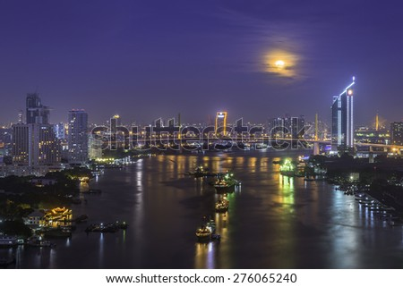 Moon rise over midtown Bangkok with city skyline at night - stock photo