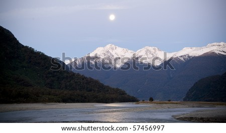 Moon rises over snow capped mountains with river in foreground