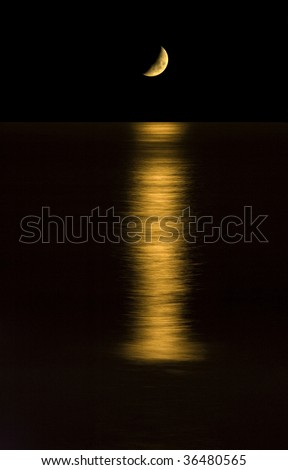 Moon setting over the ocean. - stock photo