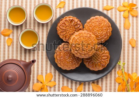 Mooncake and tea,food and drink for Chinese mid autumn festival. Traditional mooncakes on table setting with teapot. - stock photo
