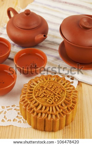 Mooncake and tea set on table. Mooncake traditionally eaten during the Mid-Autumn Festival. Chinese word on mooncake means single yolk lotus paste - stock photo