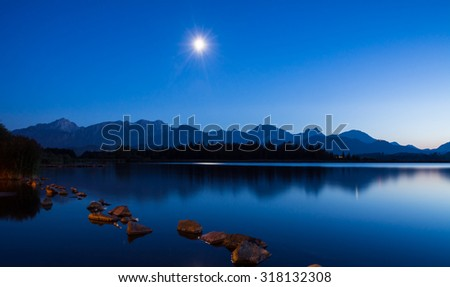 Moonlight during the blue hour at Lake Hopfen (Bavaria, Germany) - stock photo