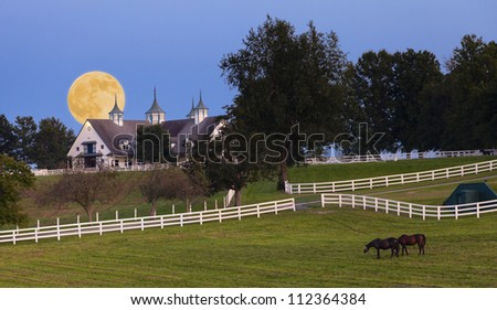 Moonrise over horse farm - stock photo