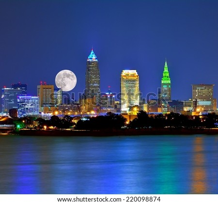 Moonrise over the Cleveland Ohio skyline with city lights reflecting onto Lake Erie in the foreground. - stock photo