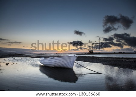 Moored dinghy at sunset - stock photo