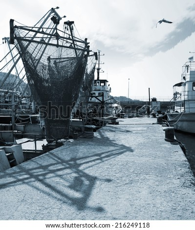Moored fishing boats with drying nets. Monochrome photo - stock photo
