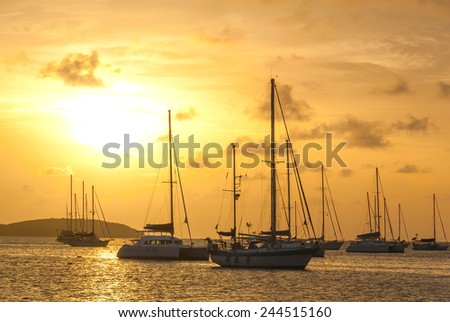 Moored sailboats in a St. Martin Harbor at sunset II. - stock photo
