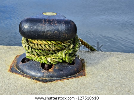 Mooring bollard with blue rope in marina of Klaipeda, Lithuania - stock photo