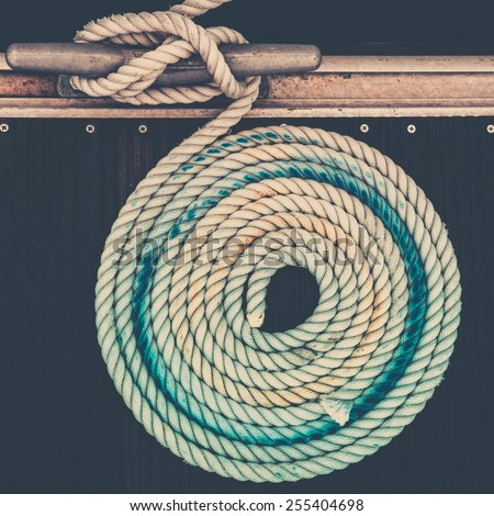 Mooring rope with a knotted end tied around a cleat on a pier - stock photo