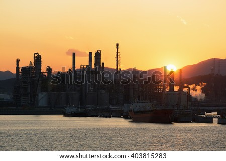 Moorings and the territory of oil refinery, with the serving vessels at sunset.