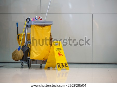 Mop bucket and caution sign. - stock photo
