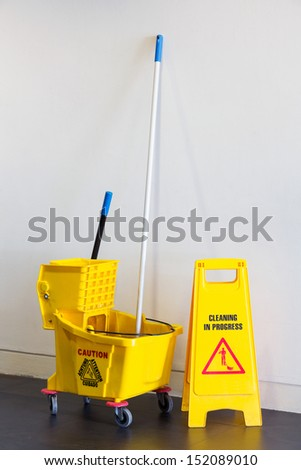 Mop bucket and wringer with caution sign on black floor in office building - stock photo