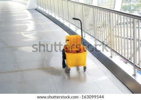 Mop bucket on floor in office building. - stock photo