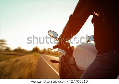 Moped drivers on road at sunset - Travel by motorcycle Concept - stock photo