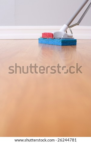 Mopping hardwood floor with a sponge mop - stock photo