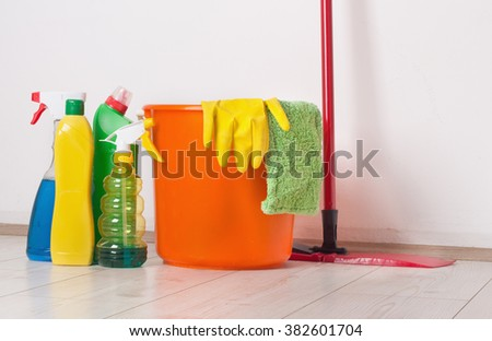 Mopping stick, bucket and cleaning supplies standing on bright wooden floor beside white wall - stock photo