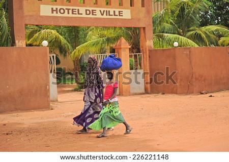 MOPTI, MALI, AFRICA - AUGUST, 26, 2011 African women walking along one of the main streets of Mopti - stock photo