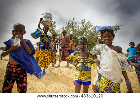MOPTI, MALI - DEC 31: Unidentified kids walking in the countryside, a young girl is carrying kitchenware on her head, pure African tradition. Lifestyle around Mopti in Mali 2012.