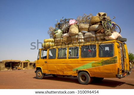 MOPTI, MALI, JANUARY 2, 2011: Old and overloaded public transport with goods on its roof. The way the migrants use to travel to the borders of Europe. - stock photo