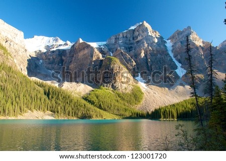 Moraine Lake, Canada, in the warm evening light with two kayaks under a majestic mountain range