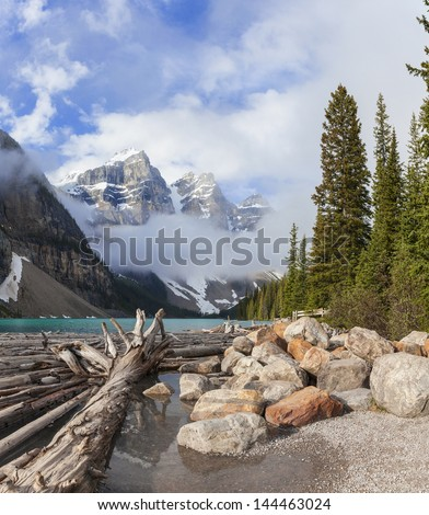 Moraine Lake, glacially-fed lake, Banff National Park, Alberta, Canada, in the Valley of the Ten Peaks. Surrounded by snow covered peaks of the Rocky Mountains with logs floating in the foreground. - stock photo