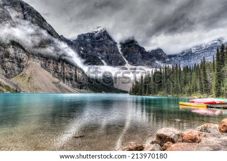 Moraine Lake with clouds descending on the Valley of the Ten Peaks in the background and some canoes on the lake. HDR rendering. - stock photo