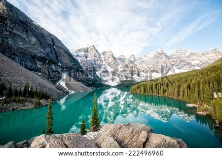 Moraine Lake with still water, viewed in early morning light - stock photo