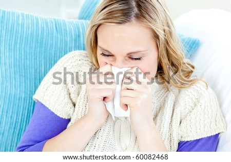 Morbid woman using a tissue sitting on a sofa at home - stock photo