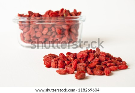 more red Wolf berry in glass cup and white paper background - stock photo