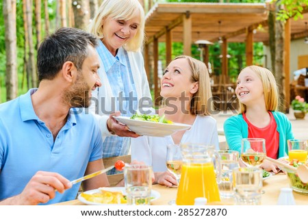 More salad? Happy family enjoying meal together while sitting at the dining table outdoors  - stock photo